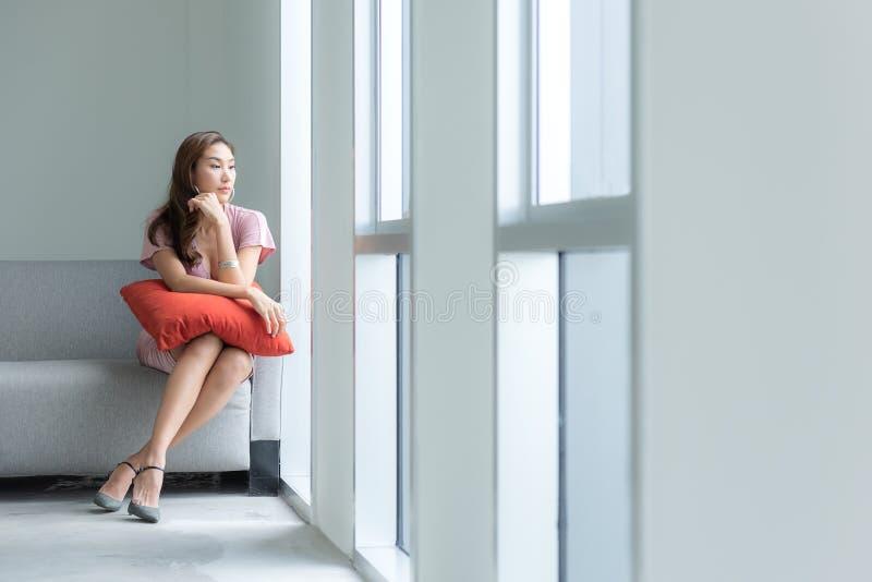 Ασιατικές όμορφες χαλάρωση και ψύχρα γυναικών στον καναπέ κοντά στο παράθυρο στο καθιστικό στοκ εικόνα με δικαίωμα ελεύθερης χρήσης