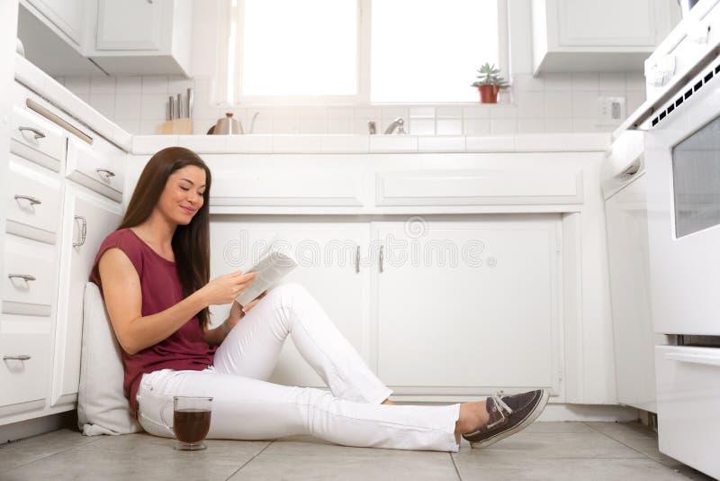Ασιατική αμερικανική συνεδρίαση γυναικών στο καθαρό πάτωμα κουζινών του μικροσκοπικού σπιτιού της, που απολαμβάνει τον ελεύθερο χ στοκ εικόνα με δικαίωμα ελεύθερης χρήσης