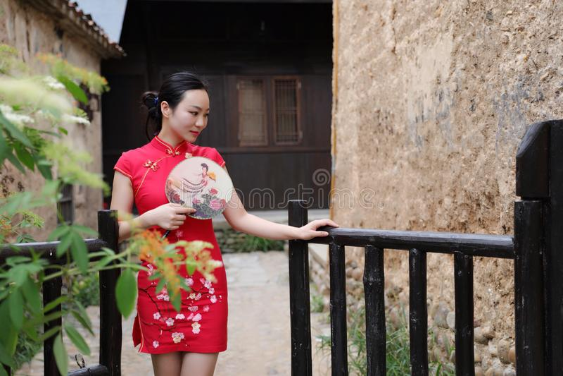Ασιατική ανατολική ασιατική κινεζική ομορφιά γυναικών στο παραδοσιακό αρχαίο κόκκινο cheongsam κοστουμιών φορεμάτων στην αρχαία μ στοκ φωτογραφία