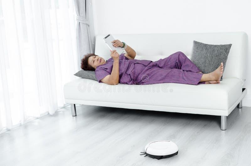 Ασιατική ανώτερη γυναίκα που βρίσκεται στον καναπέ και που χρησιμοποιεί την ταμπλέτα Vacuu ρομπότ στοκ εικόνα με δικαίωμα ελεύθερης χρήσης