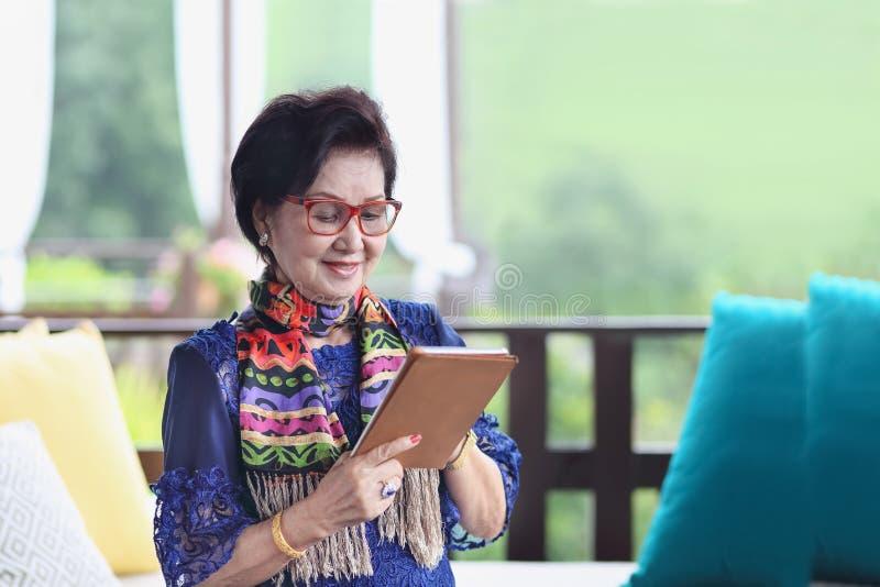 Ασιατική ανώτερη γυναίκα που κάθεται και που χρησιμοποιεί μια ταμπλέτα στοκ εικόνες με δικαίωμα ελεύθερης χρήσης