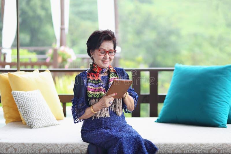Ασιατική ανώτερη γυναίκα που κάθεται και που χρησιμοποιεί μια ταμπλέτα στοκ εικόνες