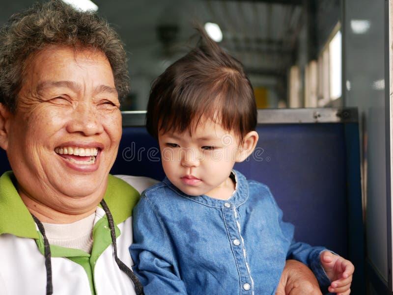 Ασιατική γιαγιά που γελά και που χαμογελά απολαμβάνοντας κρατώντας την εγγονή της όπως αυτοί που ταξιδεύουν σε ένα τραίνο από κοι στοκ εικόνες με δικαίωμα ελεύθερης χρήσης