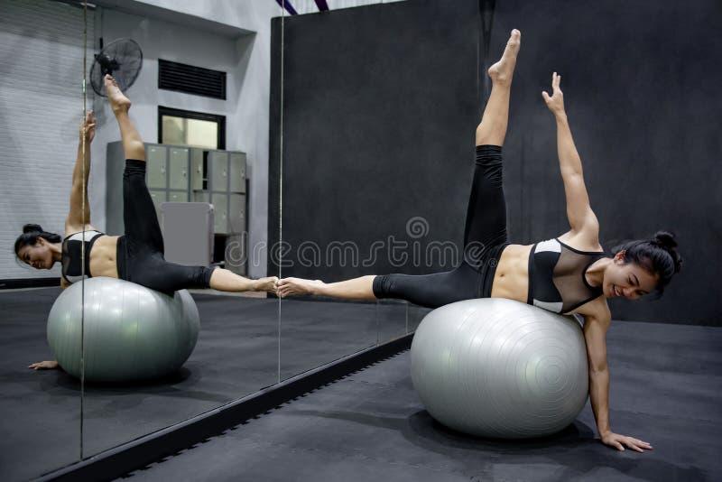 Ασιατική γυναίκα αθλητών που κάνει την άσκηση με τη σφαίρα στοκ εικόνες