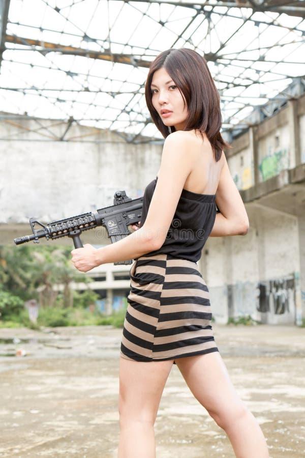 Ασιατική γυναίκα με ένα πυροβόλο όπλο στις καταστροφές στοκ φωτογραφία