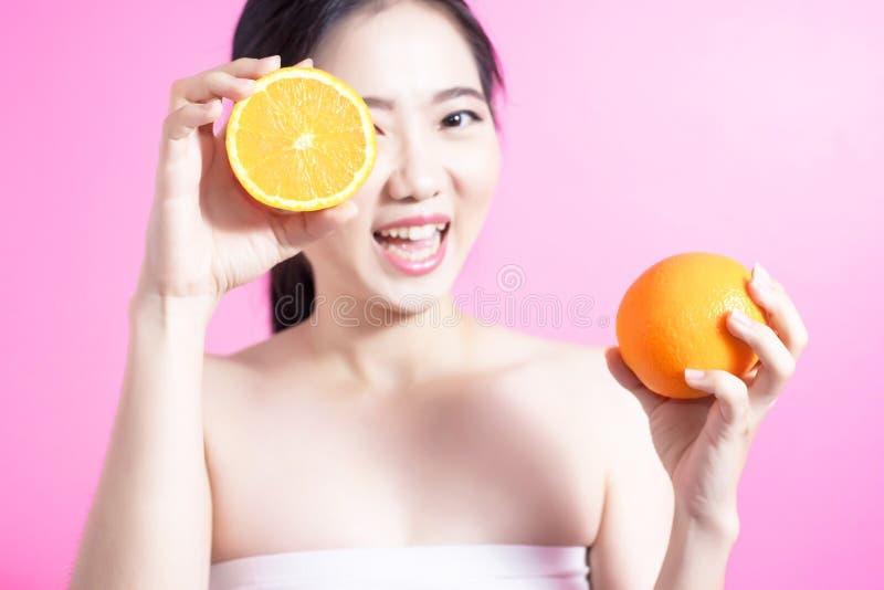 Ασιατική γυναίκα με την πορτοκαλιά έννοια Αυτή που χαμογελά και που κρατά πορτοκαλής Πρόσωπο ομορφιάς και φυσικό makeup Απομονωμέ στοκ εικόνα