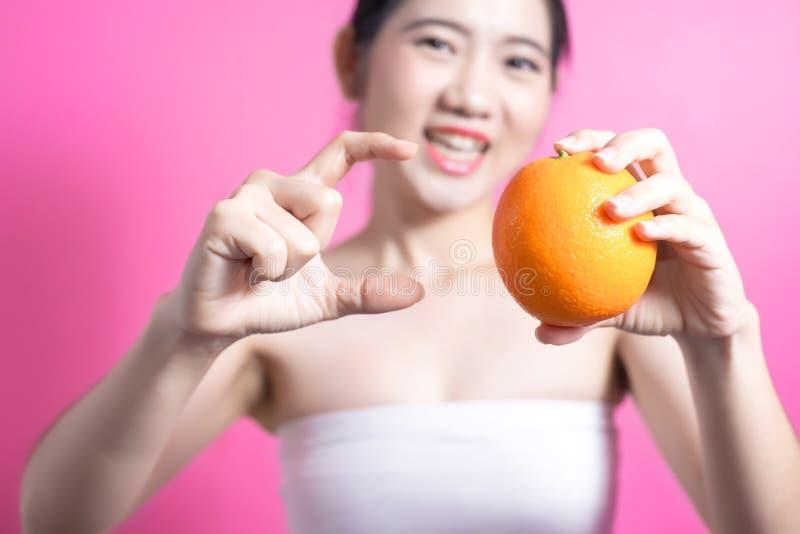 Ασιατική γυναίκα με την πορτοκαλιά έννοια Αυτή που χαμογελά και που κρατά πορτοκαλής Πρόσωπο ομορφιάς και φυσικό makeup Απομονωμέ στοκ φωτογραφίες