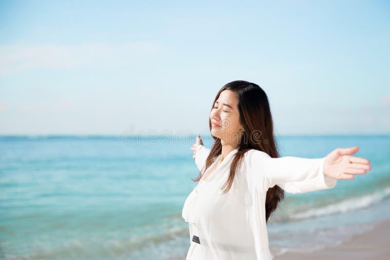 Ασιατική γυναίκα που απολαμβάνει την παραλία, τις ιδιαίτερες προσοχές και τις ανοικτές αγκάλες στοκ φωτογραφία με δικαίωμα ελεύθερης χρήσης