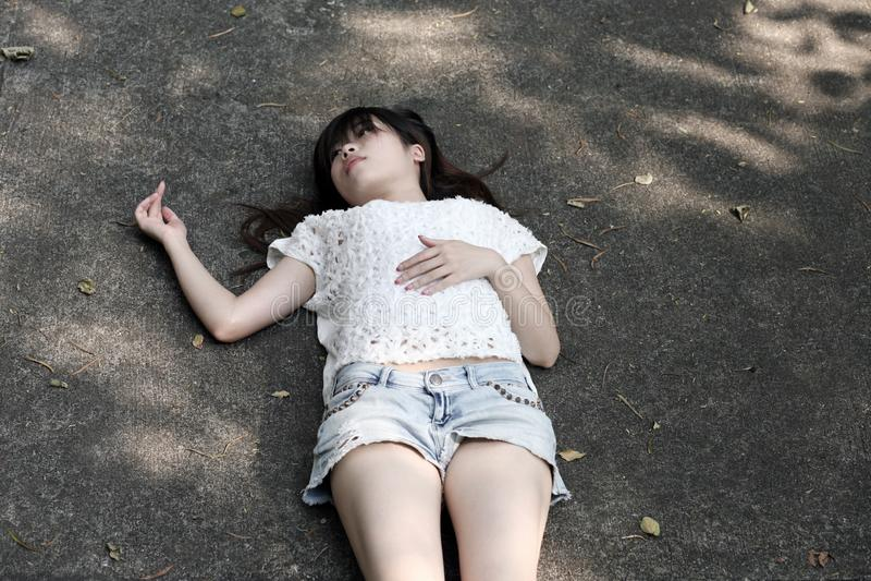 Ασιατική γυναίκα που βρίσκεται στο τραχύ πάτωμα τσιμέντου στοκ εικόνες