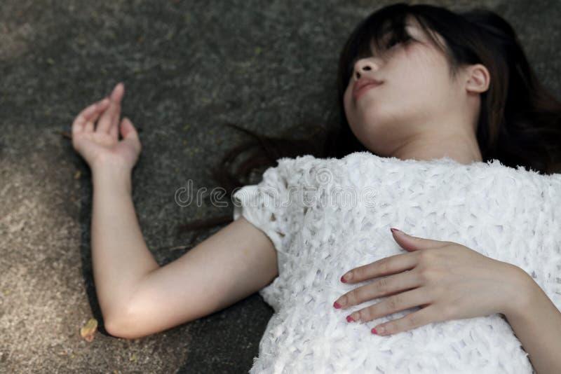 Ασιατική γυναίκα που βρίσκεται στο τραχύ πάτωμα τσιμέντου στοκ φωτογραφία με δικαίωμα ελεύθερης χρήσης
