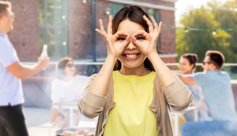 Ασιατική γυναίκα που κατασκευάζει τα γυαλιά δάχτυλων στο κόμμα στεγών στοκ εικόνες