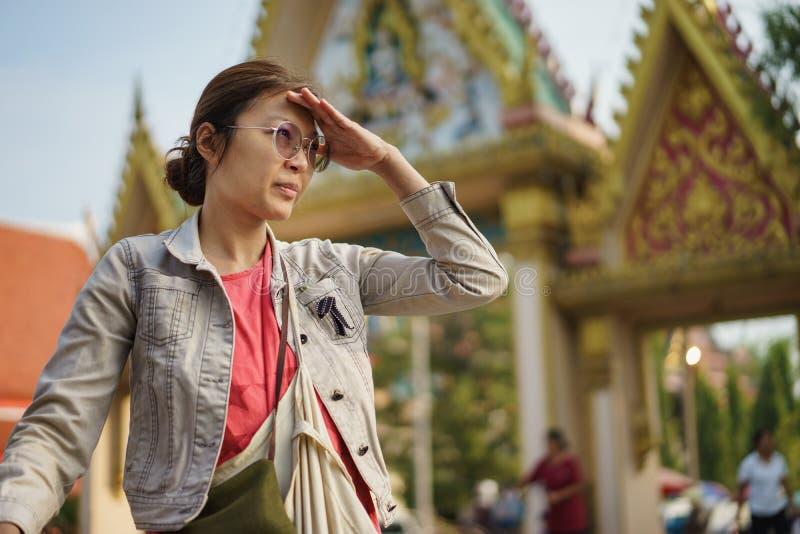 Ασιατική γυναίκα που κοιτάζει προς για κάτι με τον ταϊλανδικό ναό στοκ εικόνα με δικαίωμα ελεύθερης χρήσης