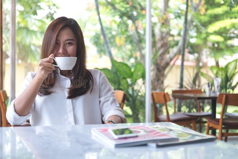 Ασιατική γυναίκα που μυρίζει και που πίνει τον καυτό καφέ με το αίσθημα καλός στον άσπρο σύγχρονο καφέ στοκ φωτογραφίες