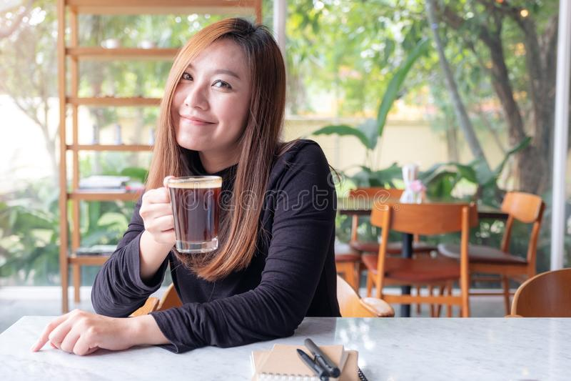 Ασιατική γυναίκα που μυρίζει και που πίνει τον καυτό καφέ με το αίσθημα καλός στον καφέ στοκ εικόνες με δικαίωμα ελεύθερης χρήσης