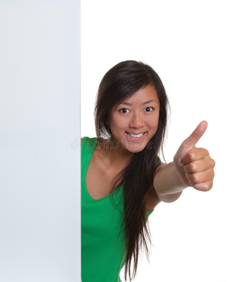 Ασιατική γυναίκα που παρουσιάζει αντίχειρα πίσω από μια πινακίδα στοκ εικόνα με δικαίωμα ελεύθερης χρήσης