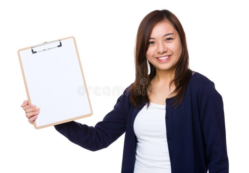 Ασιατική γυναίκα που παρουσιάζει με την κενή σελίδα της περιοχής αποκομμάτων στοκ φωτογραφία