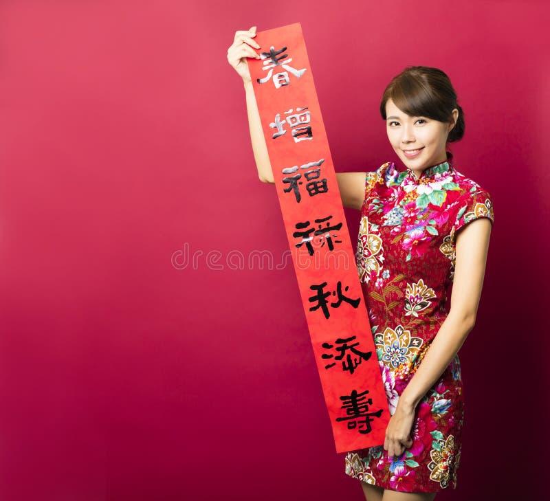 Ασιατική γυναίκα που παρουσιάζει couplets φεστιβάλ ανοίξεων στοκ φωτογραφία