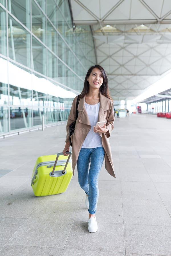 Ασιατική γυναίκα που περπατά με τις αποσκευές και που κρατά το κινητό τηλέφωνο στον οικότροφο στοκ φωτογραφίες με δικαίωμα ελεύθερης χρήσης