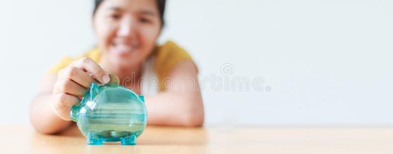 Ασιατική γυναίκα που υποβάλλει το νόμισμα χρημάτων στη σαφή piggy μεταφορά s τραπεζών στοκ εικόνα με δικαίωμα ελεύθερης χρήσης