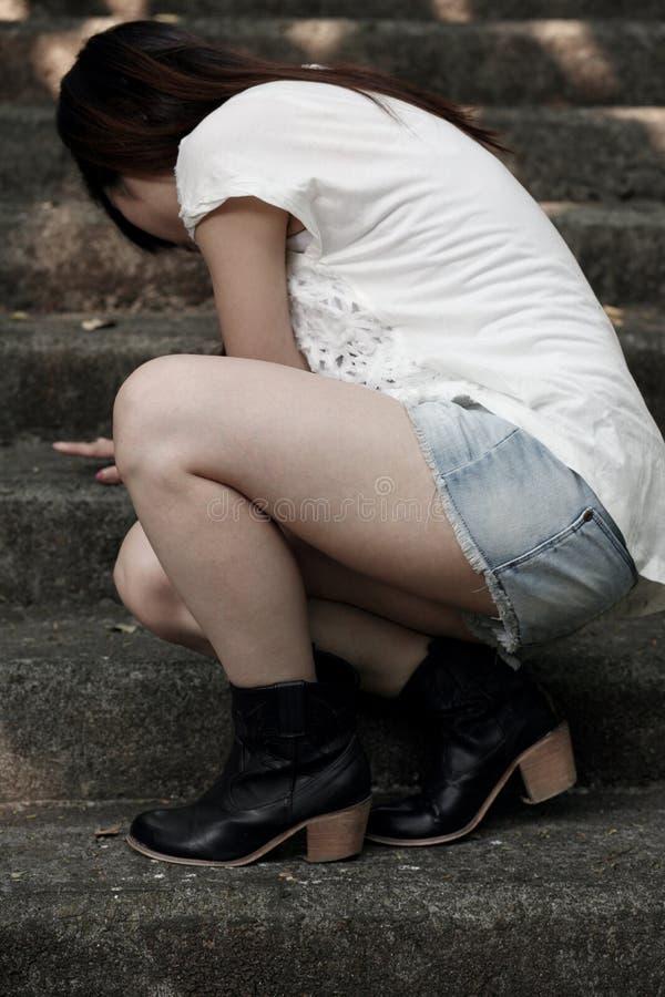Ασιατική γυναίκα που φορά τις μπότες που σκύβουν στα βήματα τσιμέντου στοκ φωτογραφία με δικαίωμα ελεύθερης χρήσης