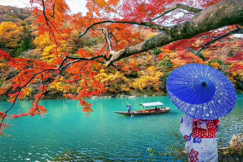 Ασιατική γυναίκα που φορά το ιαπωνικό παραδοσιακό κιμονό σε Arashiyama στην εποχή φθινοπώρου κατά μήκος του ποταμού στο Κιότο, Ια στοκ φωτογραφία