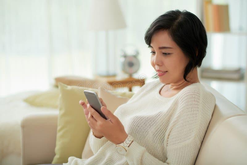Ασιατική γυναίκα που χαλαρώνει στο σπίτι να χρησιμοποιήσει Smartphone στοκ φωτογραφία με δικαίωμα ελεύθερης χρήσης