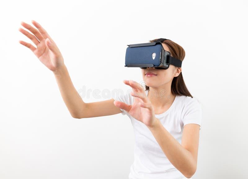 Ασιατική γυναίκα που χρησιμοποιεί την αφή κασκών εικονικής πραγματικότητας και δύο χεριών στοκ φωτογραφίες