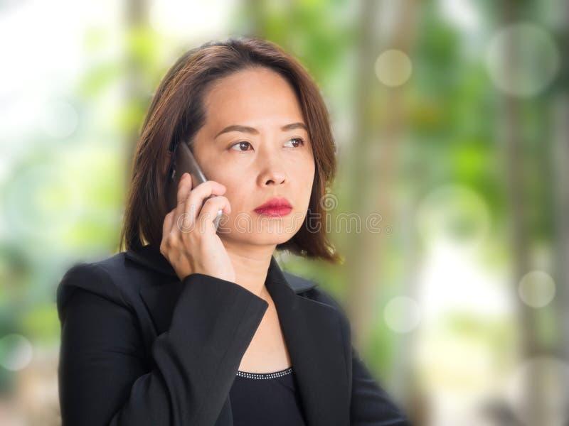 Ασιατική γυναίκα που χρησιμοποιεί το έξυπνο τηλέφωνο με το πράσινο υπόβαθρο κήπων θαμπάδων στοκ φωτογραφία με δικαίωμα ελεύθερης χρήσης