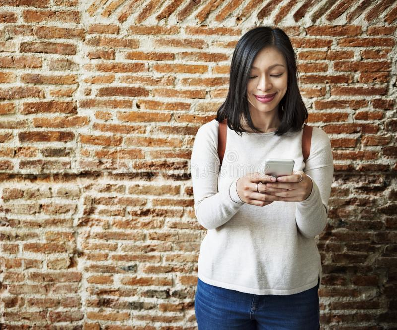 Ασιατική γυναίκα που χρησιμοποιεί το κινητό τηλέφωνο στοκ εικόνα