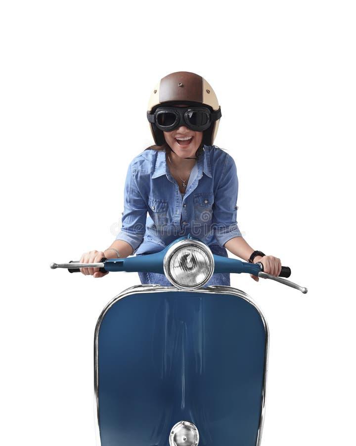 Ασιατική γυναίκα που χρησιμοποιεί το κράνος που οδηγεί την μπλε αναδρομική μοτοσικλέτα στοκ εικόνες με δικαίωμα ελεύθερης χρήσης