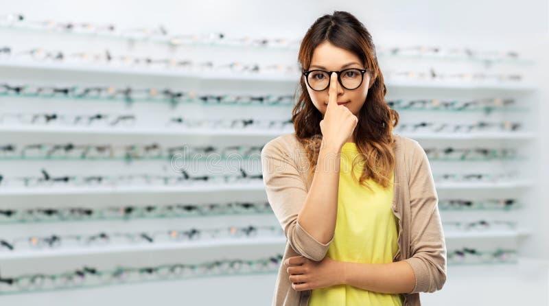 Ασιατική γυναίκα στα γυαλιά πέρα από το κατάστημα οπτικής στοκ εικόνες
