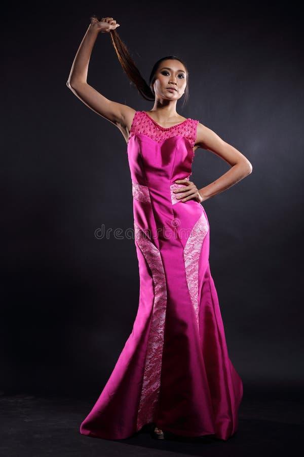 Ασιατική γυναίκα στο μακρύ φόρεμα σφαιρών βραδιού στοκ φωτογραφία
