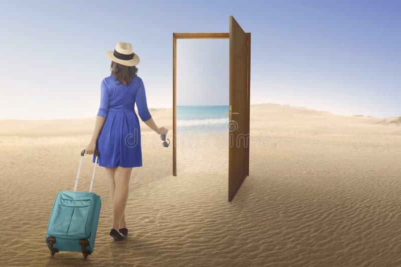 Ασιατική γυναίκα τουριστών που πηγαίνει στην παραλία στη ανοιχτή πόρτα στοκ φωτογραφίες