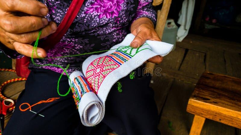 Ασιατική γυναίκα φυλών λόφων που κεντά την παραδοσιακή βιοτεχνία στοκ εικόνες