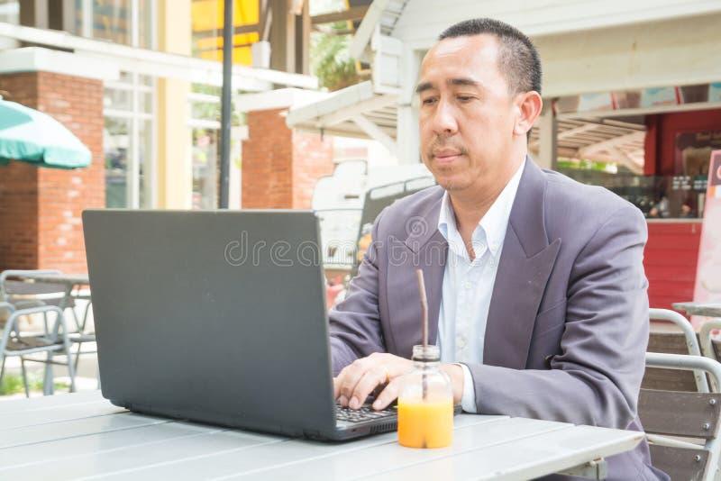 Ασιατική δακτυλογράφηση επιχειρηματιών στο σημειωματάριο ή το φορητό προσωπικό υπολογιστή στοκ φωτογραφία με δικαίωμα ελεύθερης χρήσης