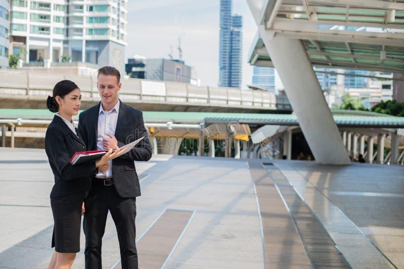 Ασιατική επιχειρηματίας και καυκάσιο ζήτημα συζήτησης επιχειρηματιών επιχειρησιακό από την οικονομική έκθεση σχετικά με χαρτί στοκ εικόνες