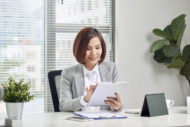 Ασιατική επιχειρηματίας που εργάζεται με τον υπολογιστή ταμπλετών στο γραφείο γραφείων στοκ εικόνες με δικαίωμα ελεύθερης χρήσης