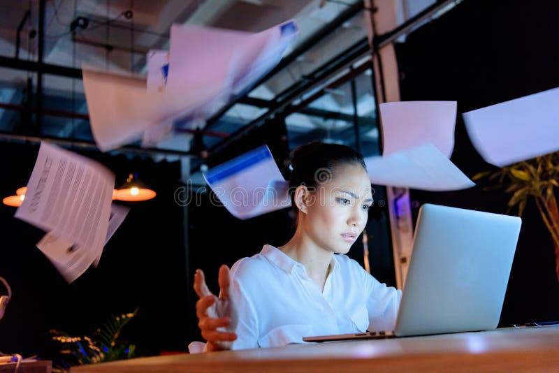 Ασιατική επιχειρηματίας που εργάζεται στο lap-top και που ρίχνει τα έγγραφα στοκ εικόνα