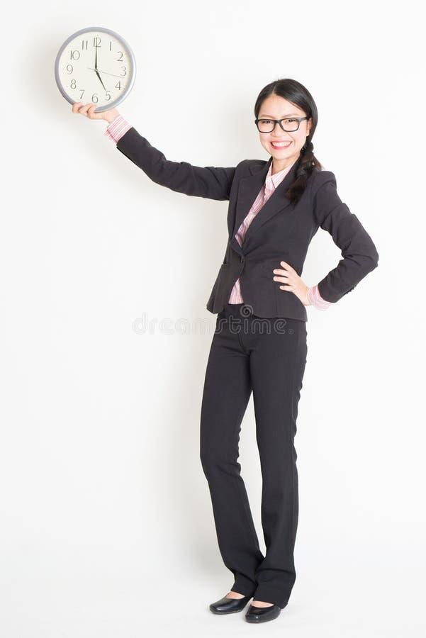 Ασιατική επιχειρηματίας που παρουσιάζει ρολόι 5pm στοκ φωτογραφία με δικαίωμα ελεύθερης χρήσης