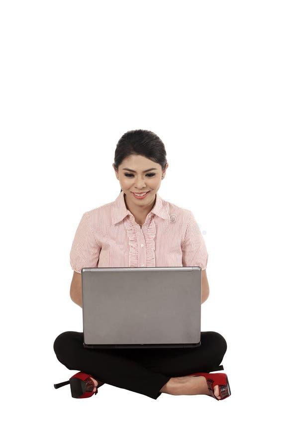 Ασιατική επιχειρησιακή γυναίκα που εργάζεται σε ένα lap-top και που κάθεται στο floo στοκ φωτογραφία με δικαίωμα ελεύθερης χρήσης