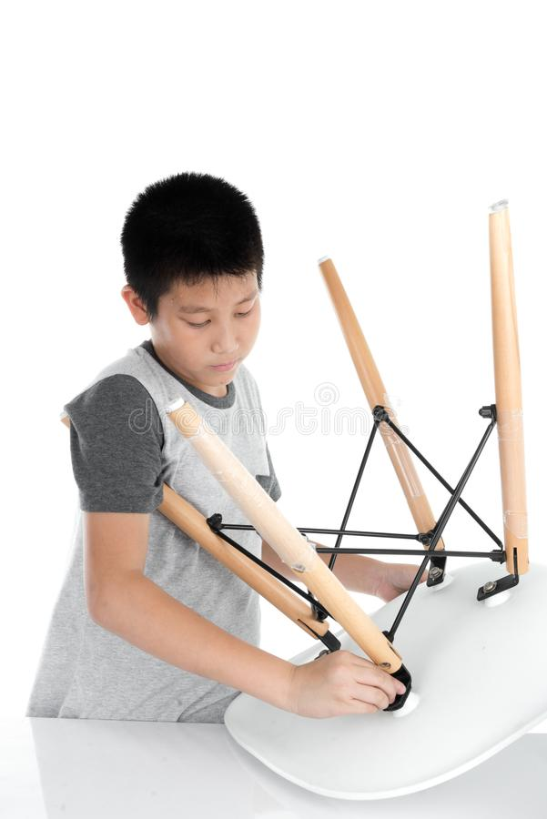 Ασιατική καρέκλα ποδιών επισκευής αγοριών στο άσπρο backgorund στοκ φωτογραφίες με δικαίωμα ελεύθερης χρήσης