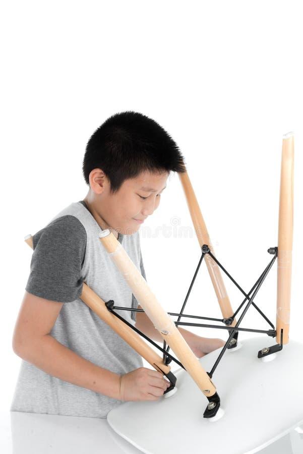 Ασιατική καρέκλα ποδιών επισκευής αγοριών στο άσπρο backgorund στοκ φωτογραφία