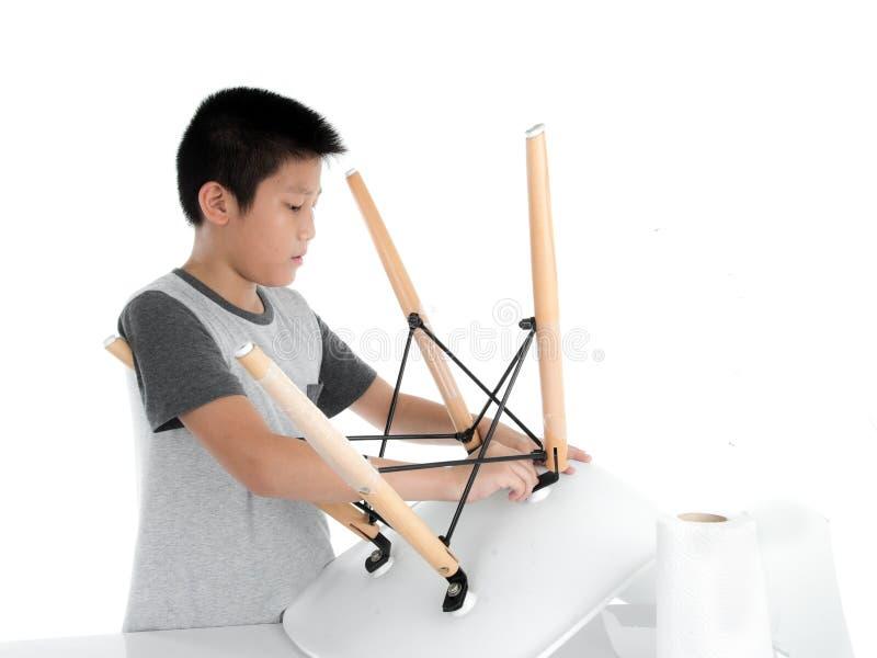 Ασιατική καρέκλα ποδιών επισκευής αγοριών στο άσπρο backgorund στοκ φωτογραφία με δικαίωμα ελεύθερης χρήσης