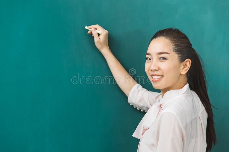 Ασιατική κιμωλία δασκάλων στον πράσινο πίνακα στοκ εικόνα