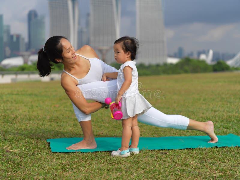 Ασιατική κινεζική γιόγκα άσκησης γυναικών υπαίθρια με το νέο μωρό gir στοκ εικόνα