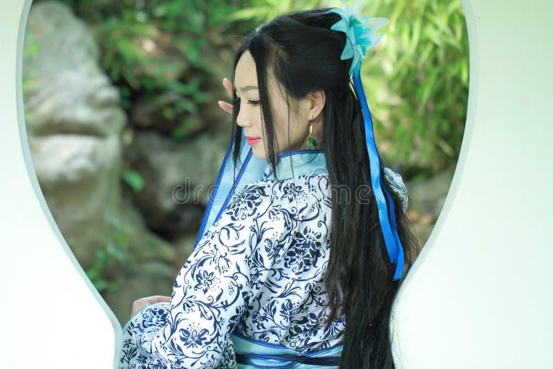 Ασιατική κινεζική γυναίκα στο παραδοσιακό μπλε και άσπρο φόρεμα Hanfu, παιχνίδι σε έναν διάσημο κήπο, στάση μπροστά από το παράθυ στοκ εικόνες με δικαίωμα ελεύθερης χρήσης