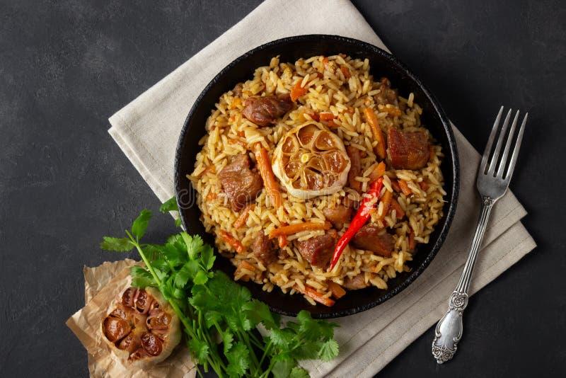 Ασιατική κουζίνα Του Ουζμπεκιστάν pilaf ή plov από το ρύζι και το κρέας σε ένα τηγάνι χυτοσιδήρου στοκ φωτογραφία