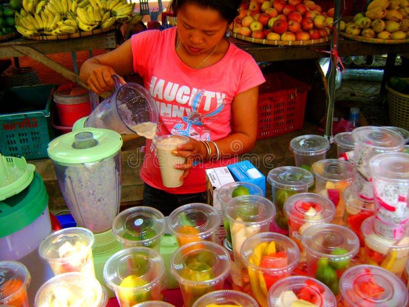 Ασιατική κυρία που κάνει το lassi φρούτων milkshakes στοκ εικόνες