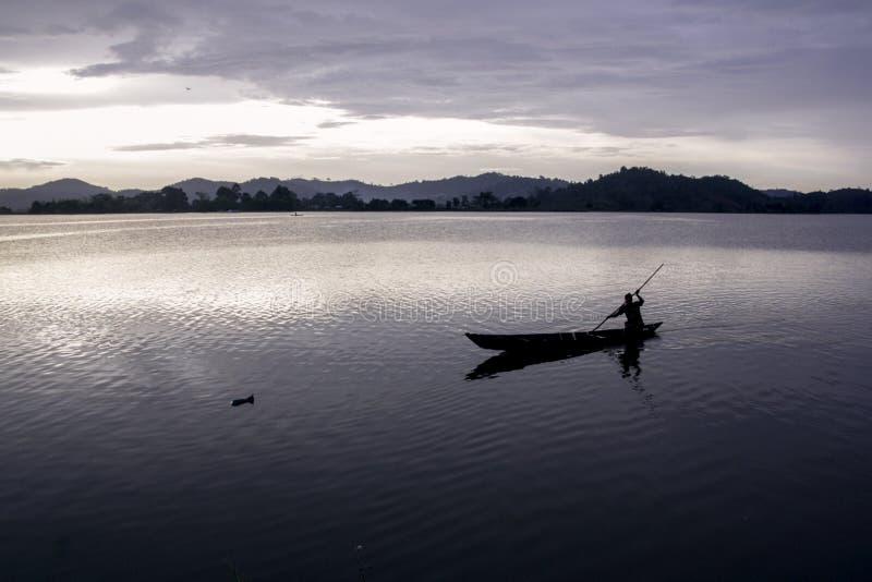 Ασιατική κωπηλασία ψαράδων πέρα από τη λίμνη στοκ εικόνα με δικαίωμα ελεύθερης χρήσης