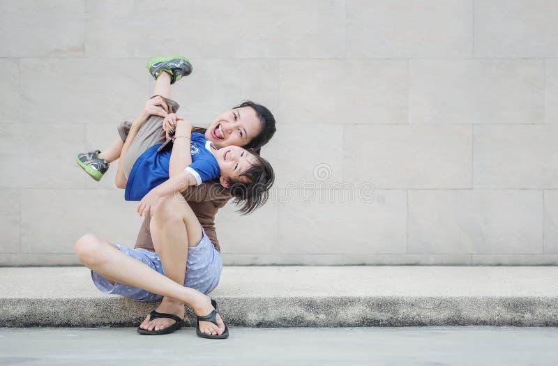 Ασιατική μητέρα κινηματογραφήσεων σε πρώτο πλάνο που κρατά το γιο της  στοκ εικόνα